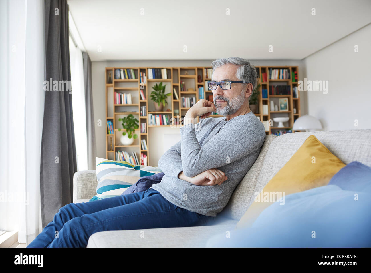 Pensive mature man sitting on couch in his living room looking out of window - Stock Image