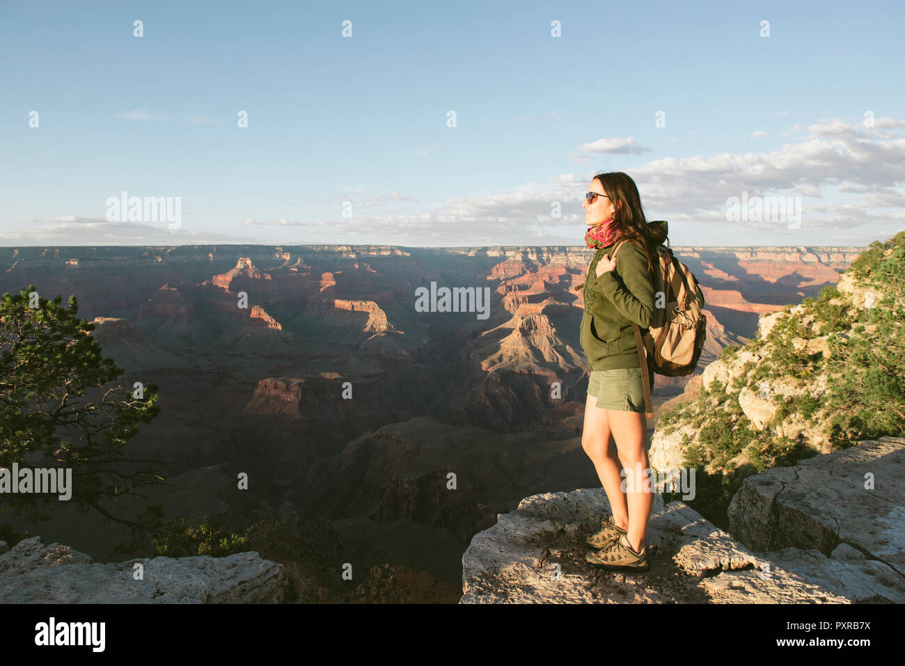USA, Arizona, Grand Canyon National Park, Young woman with backpack exploring and enjoying the landscape at sunset - Stock Image