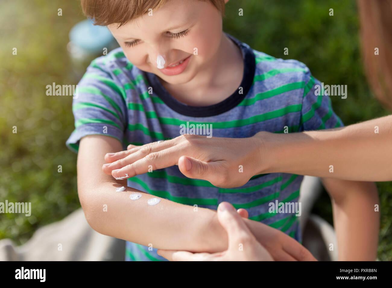 Mother applying suncream on son's arm - Stock Image