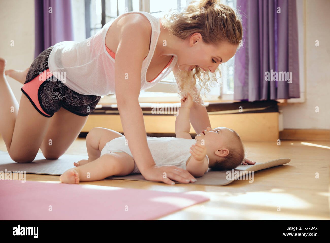 Mother playing with her baby on yoga mat while working out - Stock Image