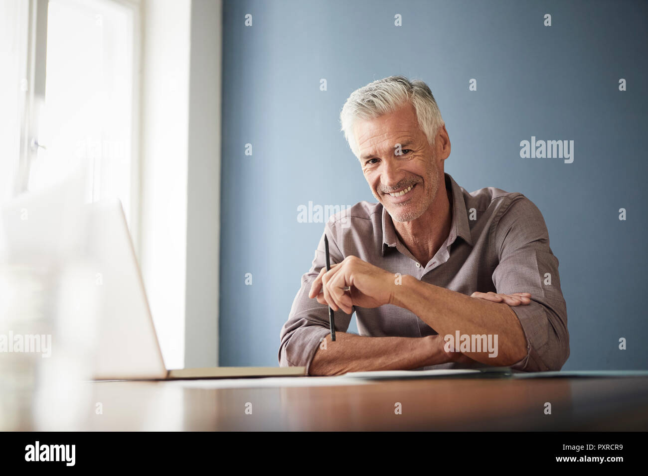 Portrait of confident mature man with laptop and documents at home - Stock Image