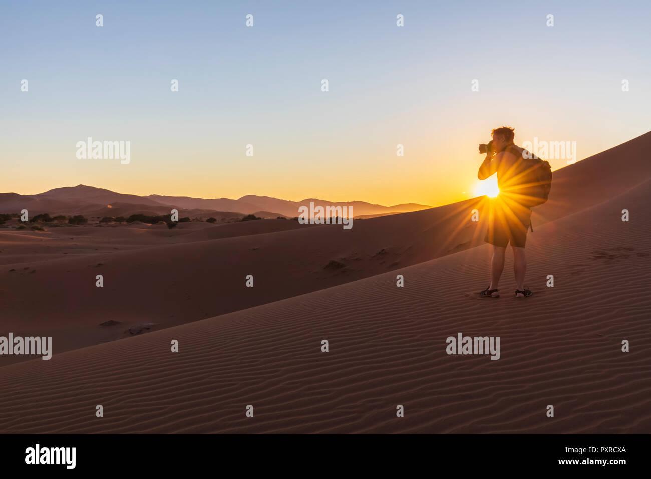Africa, Namibia, Namib desert, Naukluft National Park, photographer on dune during sunrise - Stock Image
