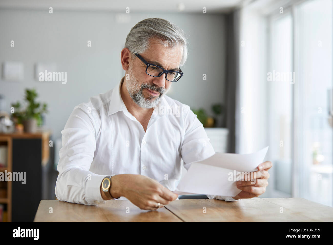 Portrait of mature man reading letter at home - Stock Image