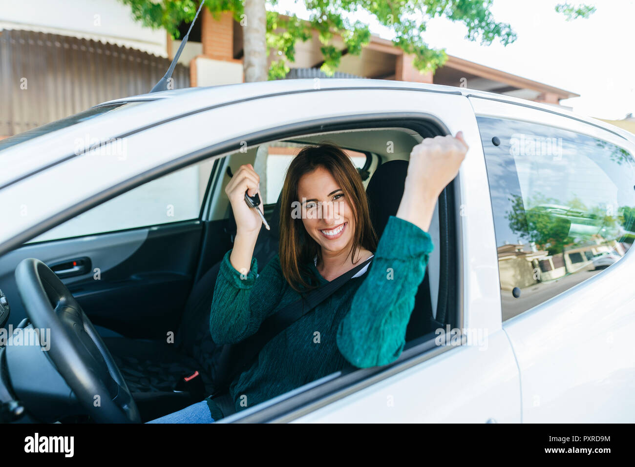 Woman inside of a car making triumph gesture - Stock Image