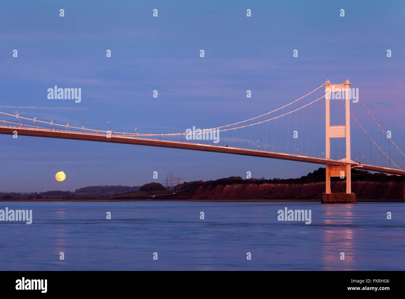 The moon rising under the old Severn Bridge, in South Gloucestershire, U.K. Built in 1966 this historic landmark and major feat of civil engineering will be abolishing its toll charges at the end of December 2018, after 52 years. - Stock Image