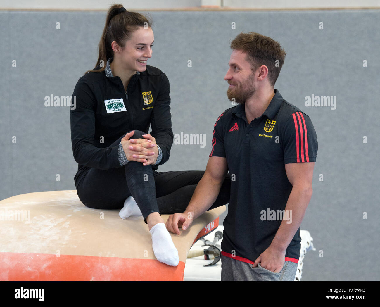 17 October 2018, Saxony, Chemnitz: Pauline Schäfer, World Champion at the balance beam and bar specialist Andreas Bretschneider in the gymnasium of the Sportforum Chemnitz. The top gymnasts from Chemnitz miss the World Championship in Doha due to injury. Schäfer is still suffering from an ankle injury. Bretschneider tore his Achilles tendon in his left foot at the German Championships in Leipzig. (to dpa-message: 'Sad pair of gymnasts: Shepherds and Bretschneider experience World Championships before TV' from 24.10.2018) Photo: Hendrik Schmidt/dpa-Zentralbild/dpa - Stock Image