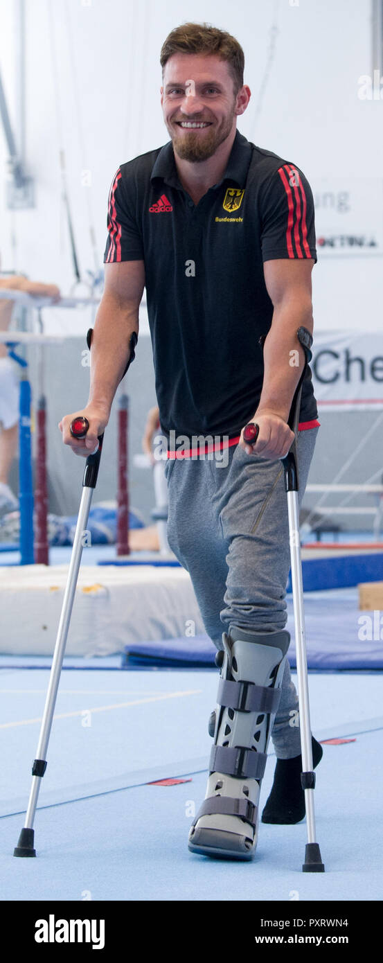 17 October 2018, Saxony, Chemnitz: High bar specialist Andreas Bretschneider goes for walking aids through the gymnasium in the Sportforum Chemnitz. Bretschneider has torn his Achilles tendon in his left foot at the German Championships in Leipzig and is now missing the World Championships in Doha. (to dpa-message: 'Sad pair of gymnasts: Shepherds and Bretschneider experience World Championships before TV' from 24.10.2018) Photo: Hendrik Schmidt/dpa-Zentralbild/dpa - Stock Image