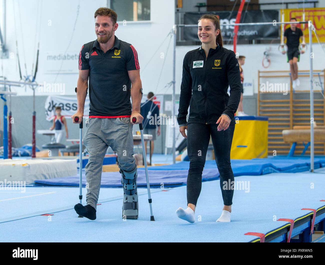 17 October 2018, Saxony, Chemnitz: High bar specialist Andreas Bretschneider goes to walking aids next to Pauline Schäfer, world champion at the balance beam, through the gymnasium in the Sportforum Chemnitz. The top gymnasts from Chemnitz miss the World Championship in Doha due to injury. Schäfer is still suffering from an ankle injury. Bretschneider tore his Achilles tendon in his left foot at the German Championships in Leipzig. (to dpa-message: 'Sad pair of gymnasts: Shepherds and Bretschneider experience World Championships before TV' from 24.10.2018) Photo: Hendrik Schmidt/dpa-Zentralbil - Stock Image