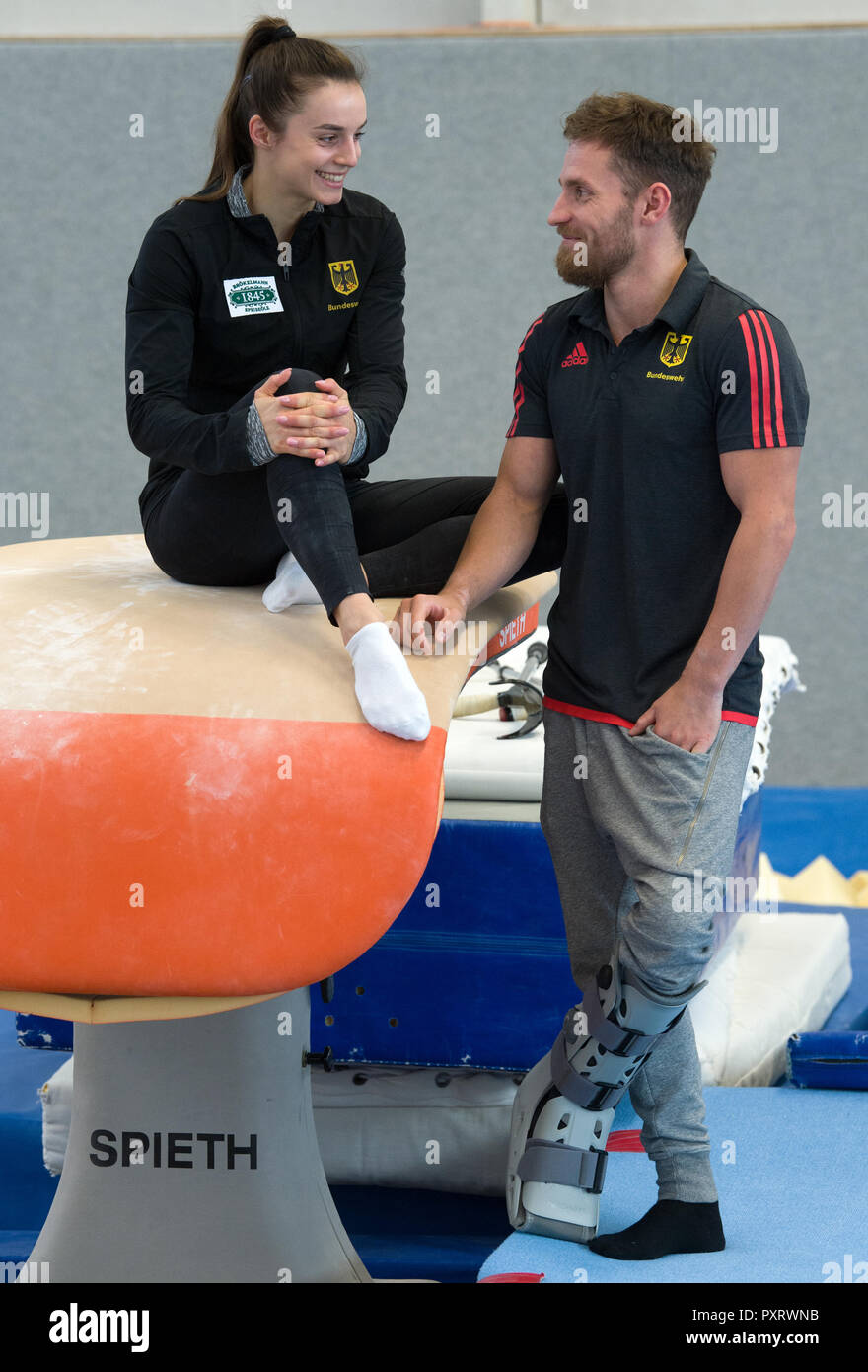 17 October 2018, Saxony, Chemnitz: Pauline Schäfer, World Champion at the balance beam and bar specialist Andreas Bretschneider talk in the gym in the Sportforum Chemnitz. The top gymnasts from Chemnitz miss the World Championship in Doha due to injury. Schäfer is still suffering from an ankle injury. Bretschneider tore his Achilles tendon in his left foot at the German Championships in Leipzig. (to dpa-message: 'Sad pair of gymnasts: Shepherds and Bretschneider experience World Championships before TV' from 24.10.2018) Photo: Hendrik Schmidt/dpa-Zentralbild/ZB - Stock Image