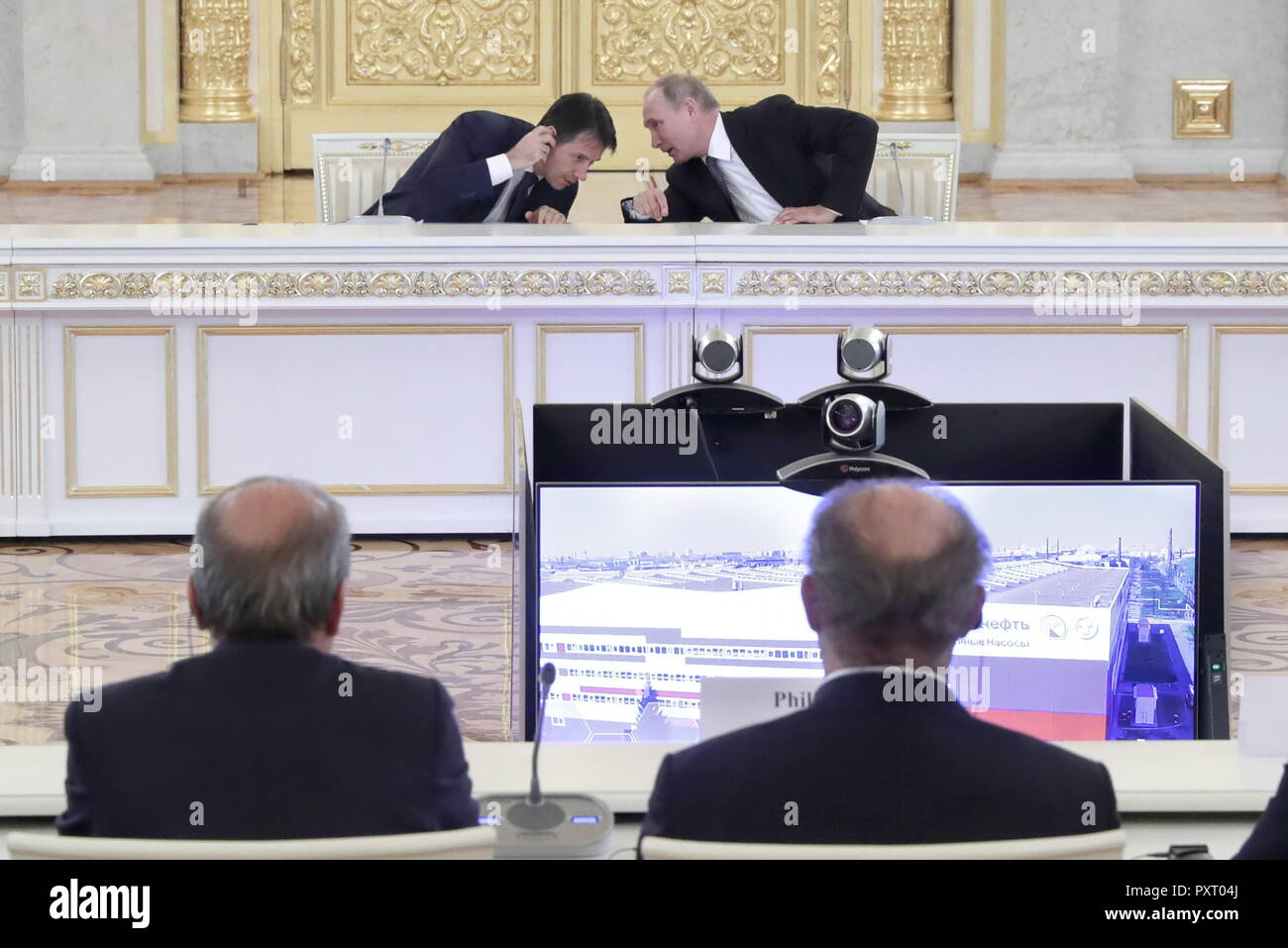 Moscow, Russia. 24th Oct, 2018. MOSCOW, RUSSIA - OCTOBER 24, 2018: The Prime Minister of Italy Giuseppe Conte (L back), and the President of Russia Vladimir Putin (R back) at a meeting of senior Russian and Italian government officials and members of Russia's and Italy's business community in the Alexander Hall of the Kremlin; those attending the meeting took part in the inauguration ceremony of a plant of the Russian Electric Motors (REM) company via a videoconference link between Moscow and Chelyabinsk. Mikhail Metzel/TASS Credit: ITAR-TASS News Agency/Alamy Live News - Stock Image