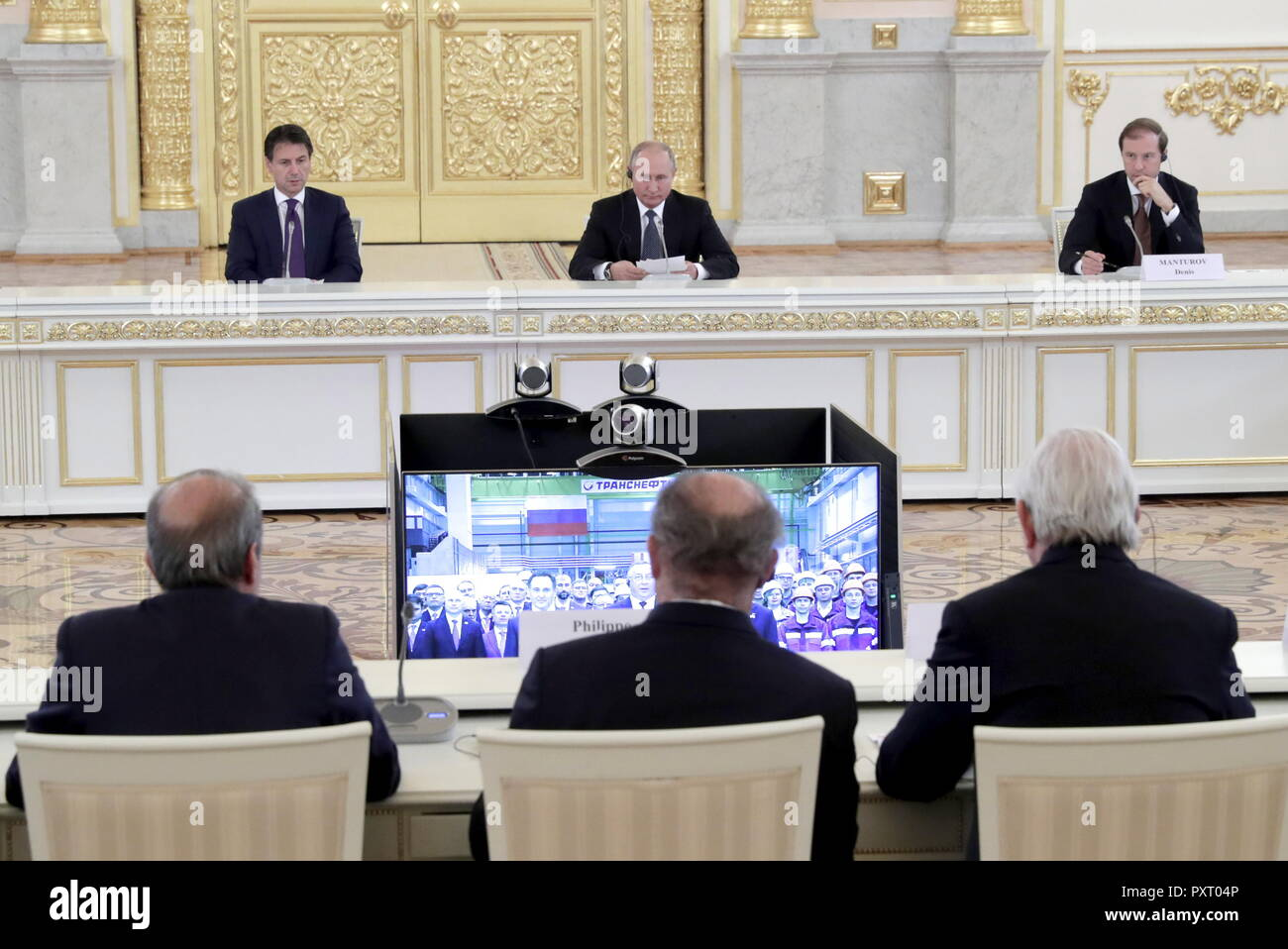 MOSCOW, RUSSIA - OCTOBER 24, 2018: The Prime Minister of Italy Giuseppe Conte, the President of Russia Vladimir Putin, and Russia's Minister of Industry and Trade Denis Manturov (L-R back) at a meeting of senior Russian and Italian government officials and members of Russia's and Italy's business community in the Alexander Hall of the Kremlin; those attending the meeting took part in the inauguration ceremony of a plant of the Russian Electric Motors (REM) company via a videoconference link between Moscow and Chelyabinsk. Mikhail Metzel/TASS - Stock Image