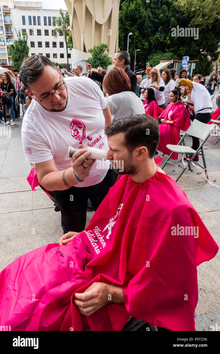 Barber brushing hair from a man nose during a free haircut - Stock Image