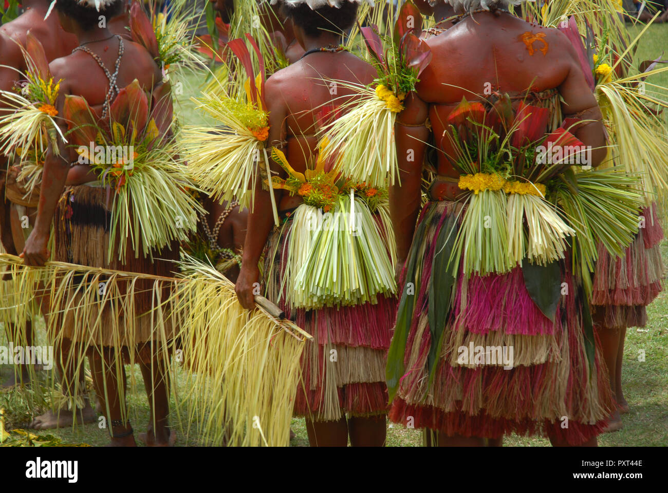 Colourfully dressed and face painted women dancing as part of a Sing Sing in Madang, Papua New Guinea. - Stock Image