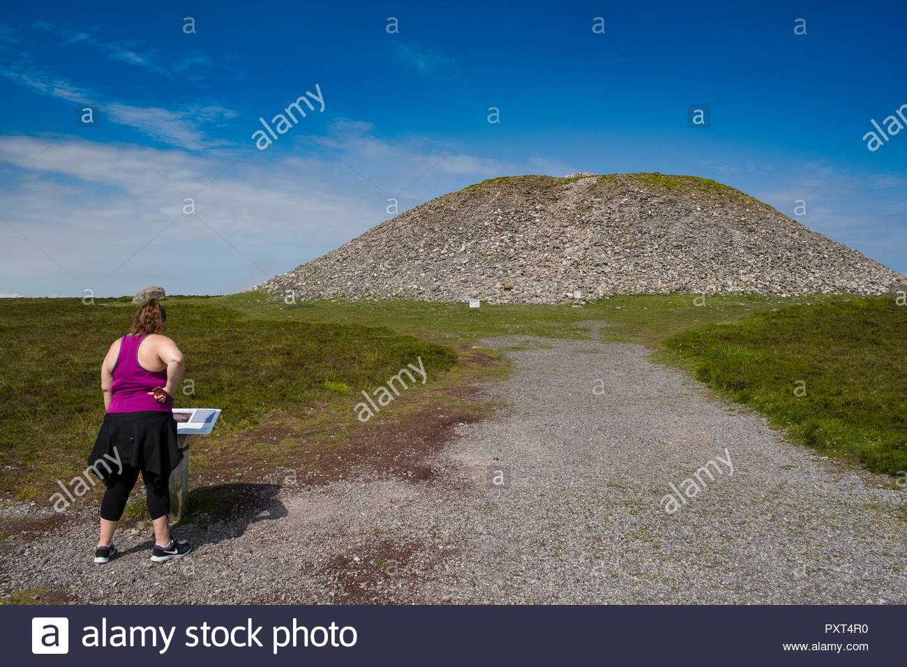 Woman reading sign with information about Queen Maeve's Grave Cairn on the summit of Knocknarea, the Neolithic passage tomb cairn measures some 180 fe Stock Photo