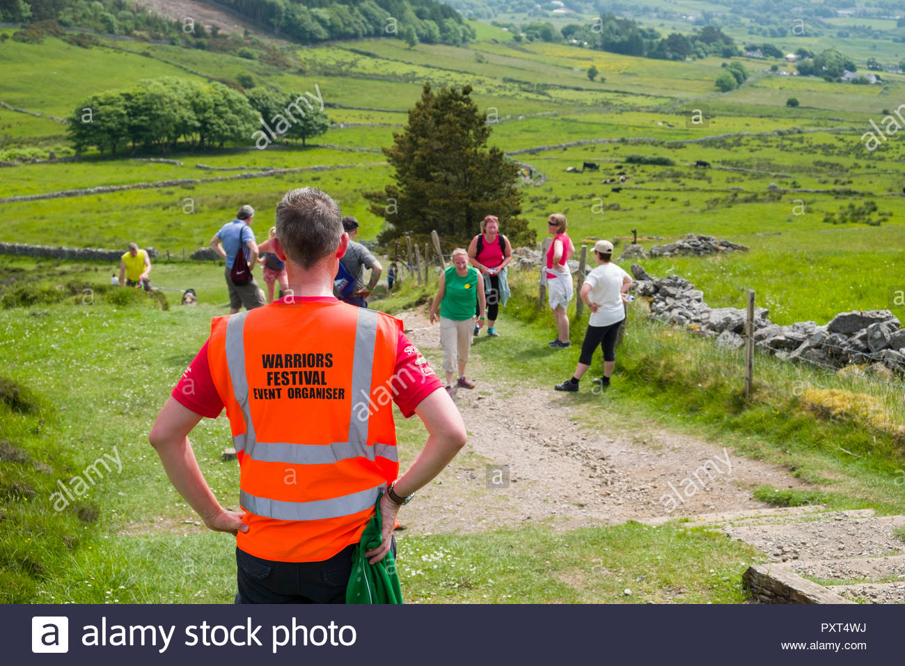 Back of man wearing high visibility vest on the Knocknarea trail, County Sligo, Connacht, Ireland - Stock Image