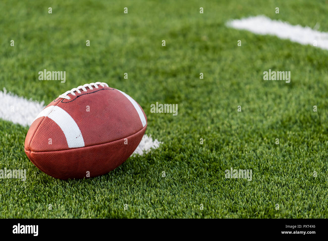 a brown leather American Football on a field - Stock Image