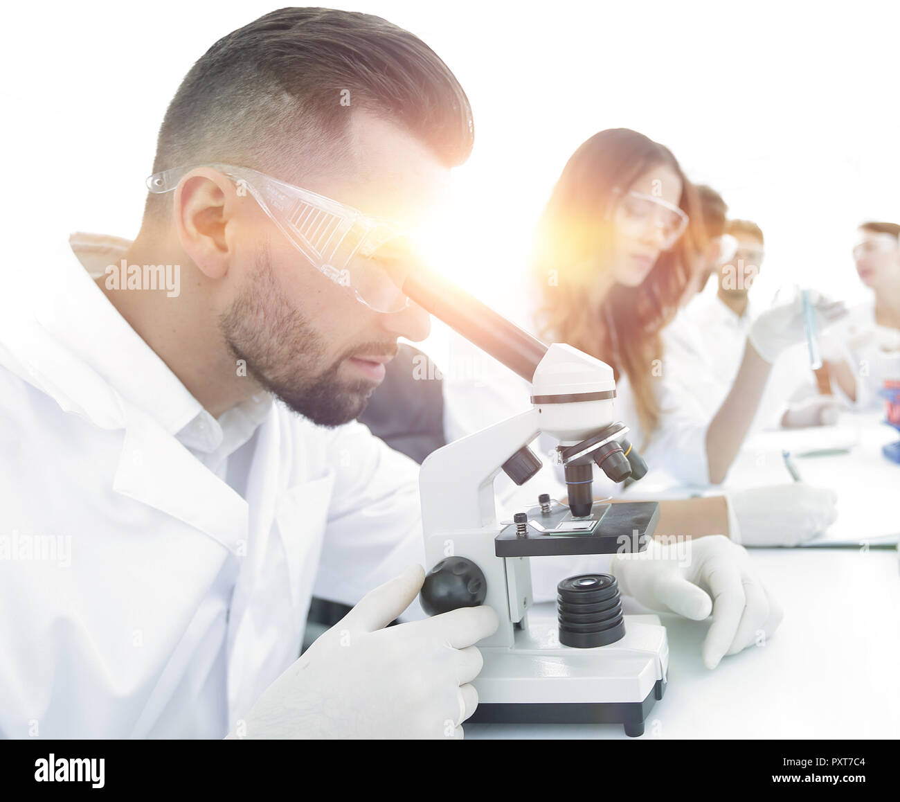 male lab technician looks at the sample under a microscope - Stock Image