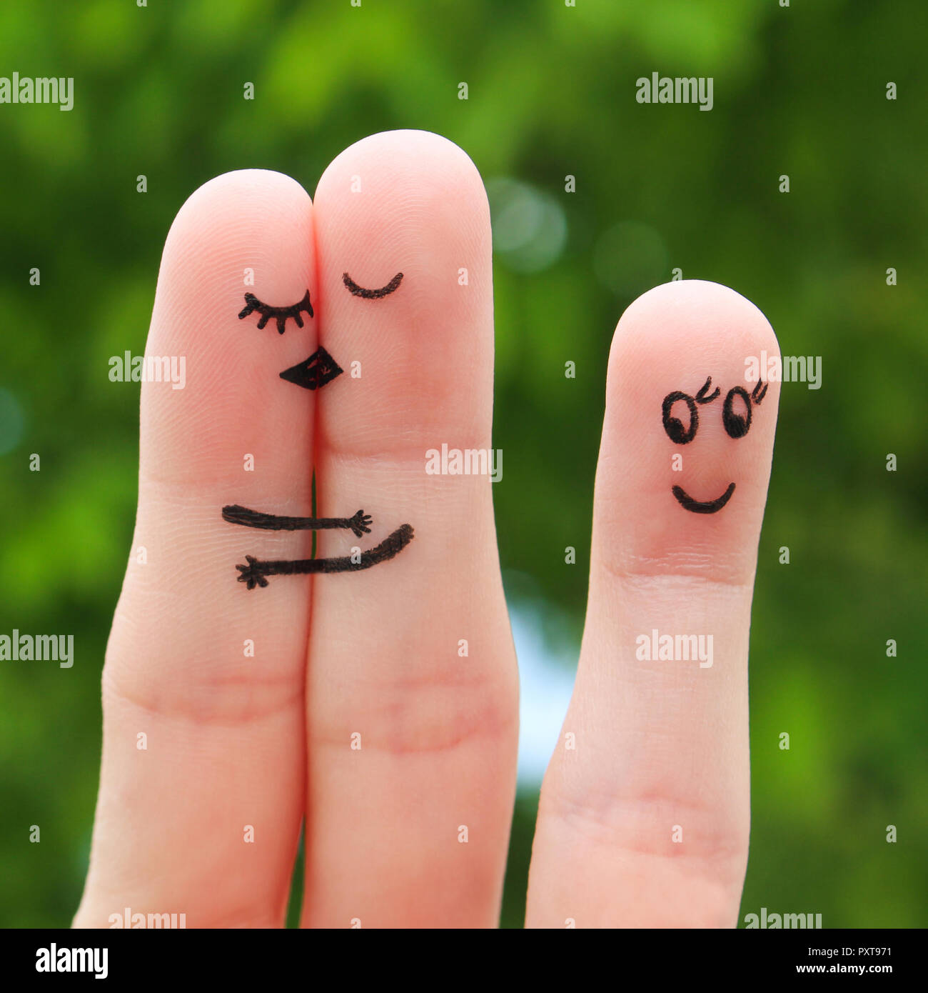Finger art of a Happy couple. The happy couple kissing and hugging. The other girl looks at them and rejoices. - Stock Image
