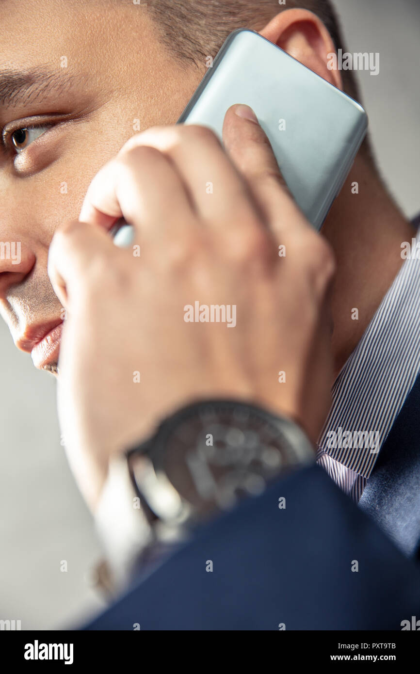 Elegant man is talking on the phone. Vertical orientation of photo - Stock Image