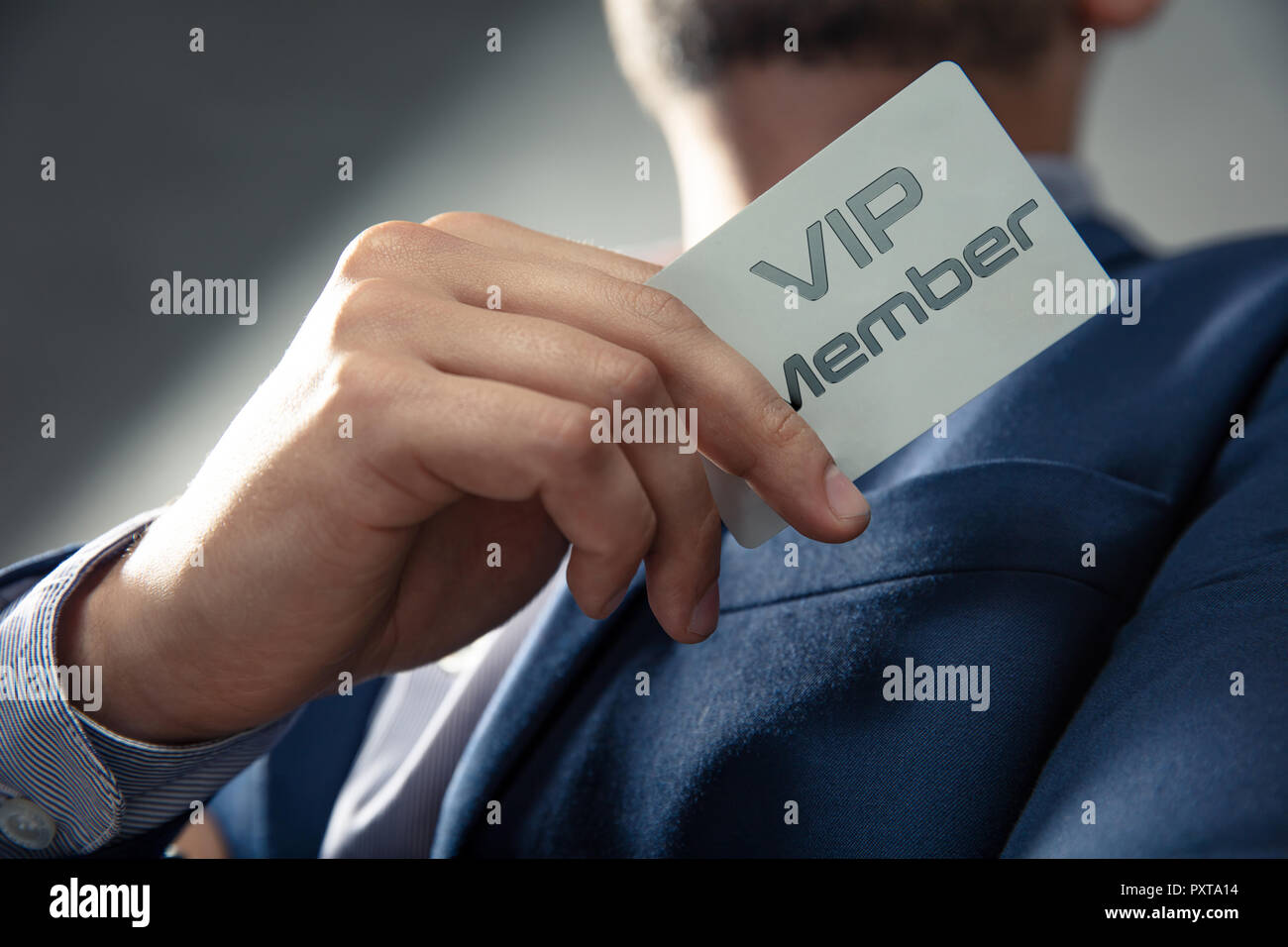 VIP member card holded by an elegant man in suit. - Stock Image