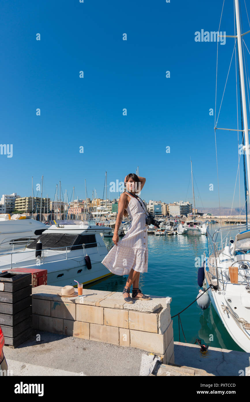 Elegant young tourist visitor woman walking on a sightseeing tour at Heraklion Venetian port, Crete, Greece  - Stock Image