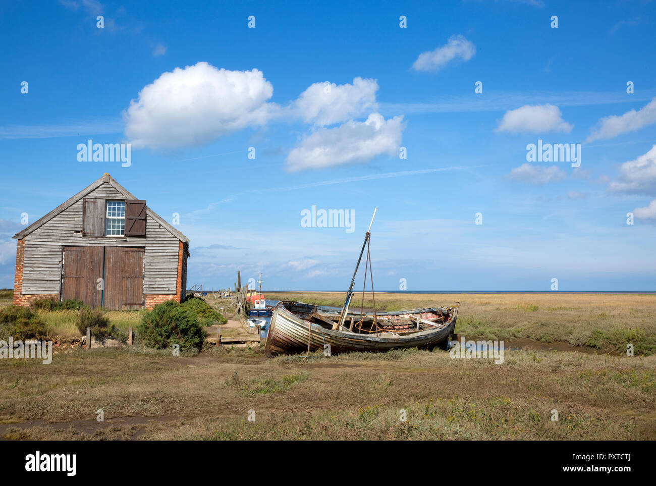 Boats and boat-house on estuary at Thornham Old Harbour, Thornham, Norfolk, England - Stock Image