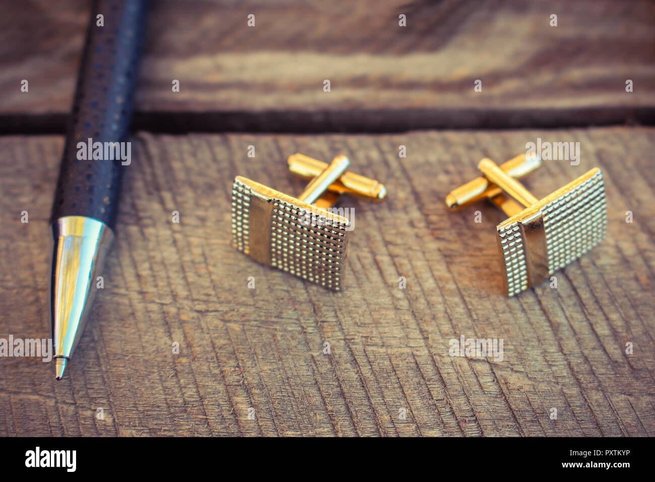 Pen, dollars and cufflinks on the old wood background - Stock Image