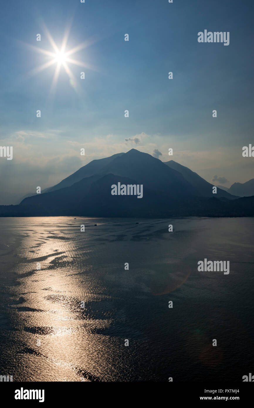 Sunstar over mountains by Lake Como in northern Italy - Stock Image