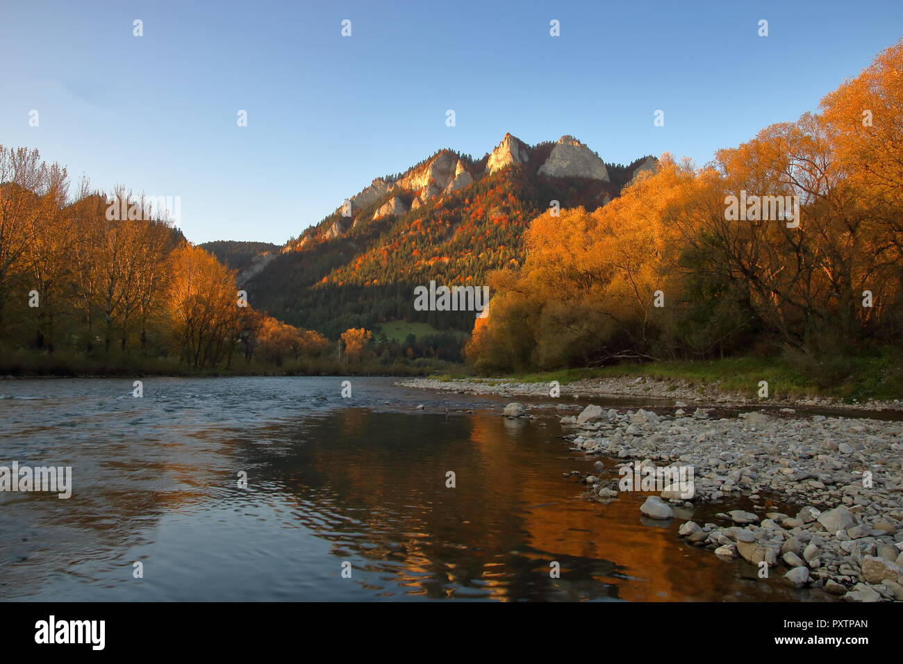 Autumnal landscape with Three Crowns massif in Pieniny mountains, Poland, Dunajec river with white stones on its riverbed, sunset light. - Stock Image