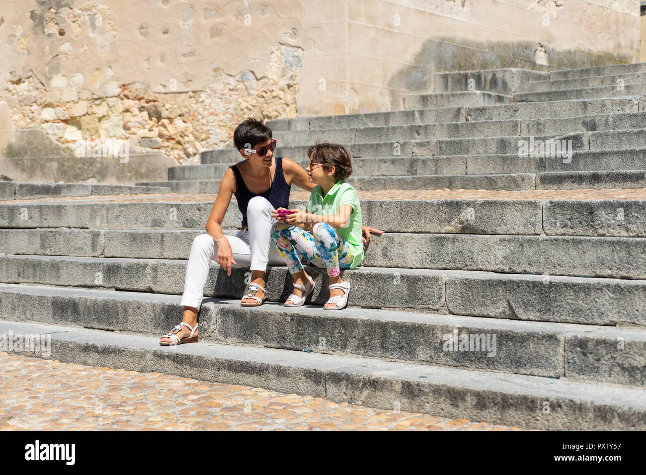 Spain, Castile and Leon, Segovia, Mother and daughter sitting on stairs - Stock Image