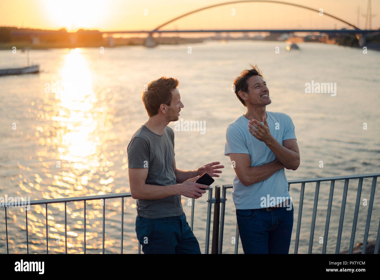 Two friends meeting at sunset, spending the evening talking - Stock Image