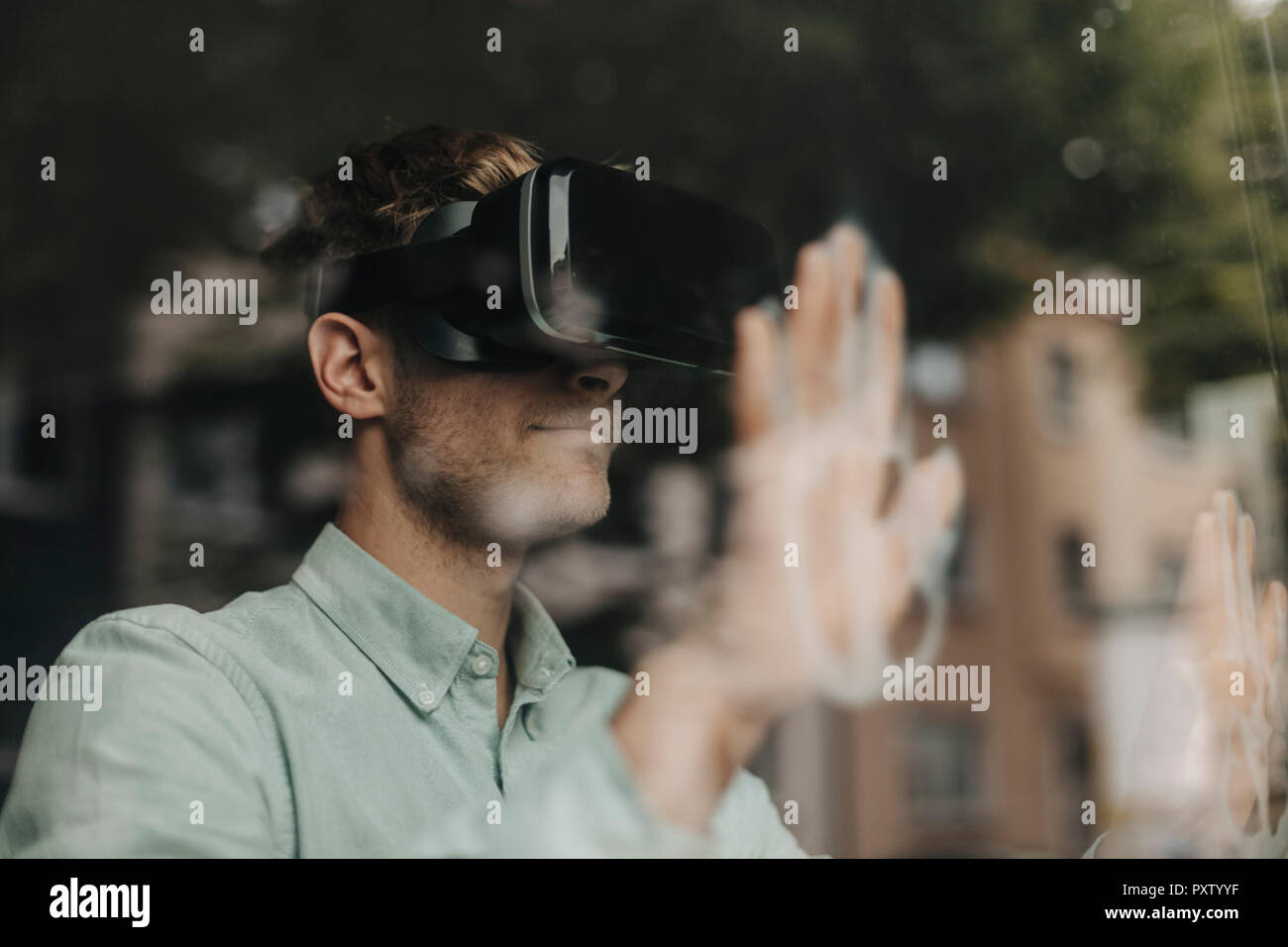 Young man standing at the window, using VR glasses - Stock Image