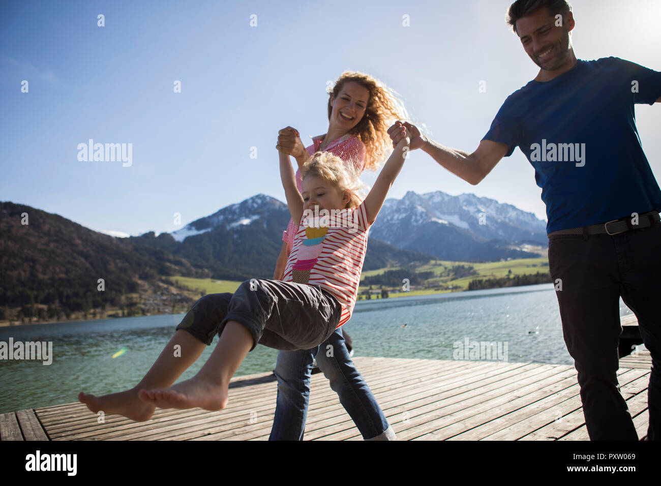 Austria, Tyrol, Walchsee, happy parents swinging their daughter at the lake - Stock Image