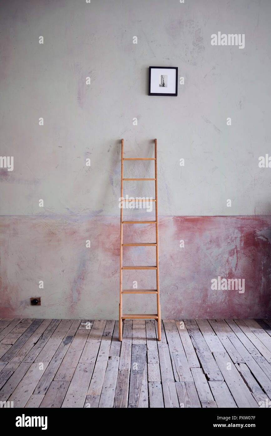 Ladder and picture in an unrenovated room in a loft - Stock Image