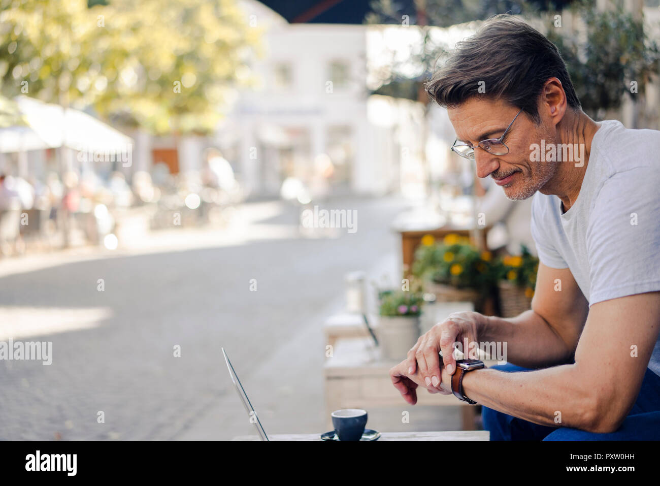 Mature businessman sitting in coffee shop, checking time - Stock Image