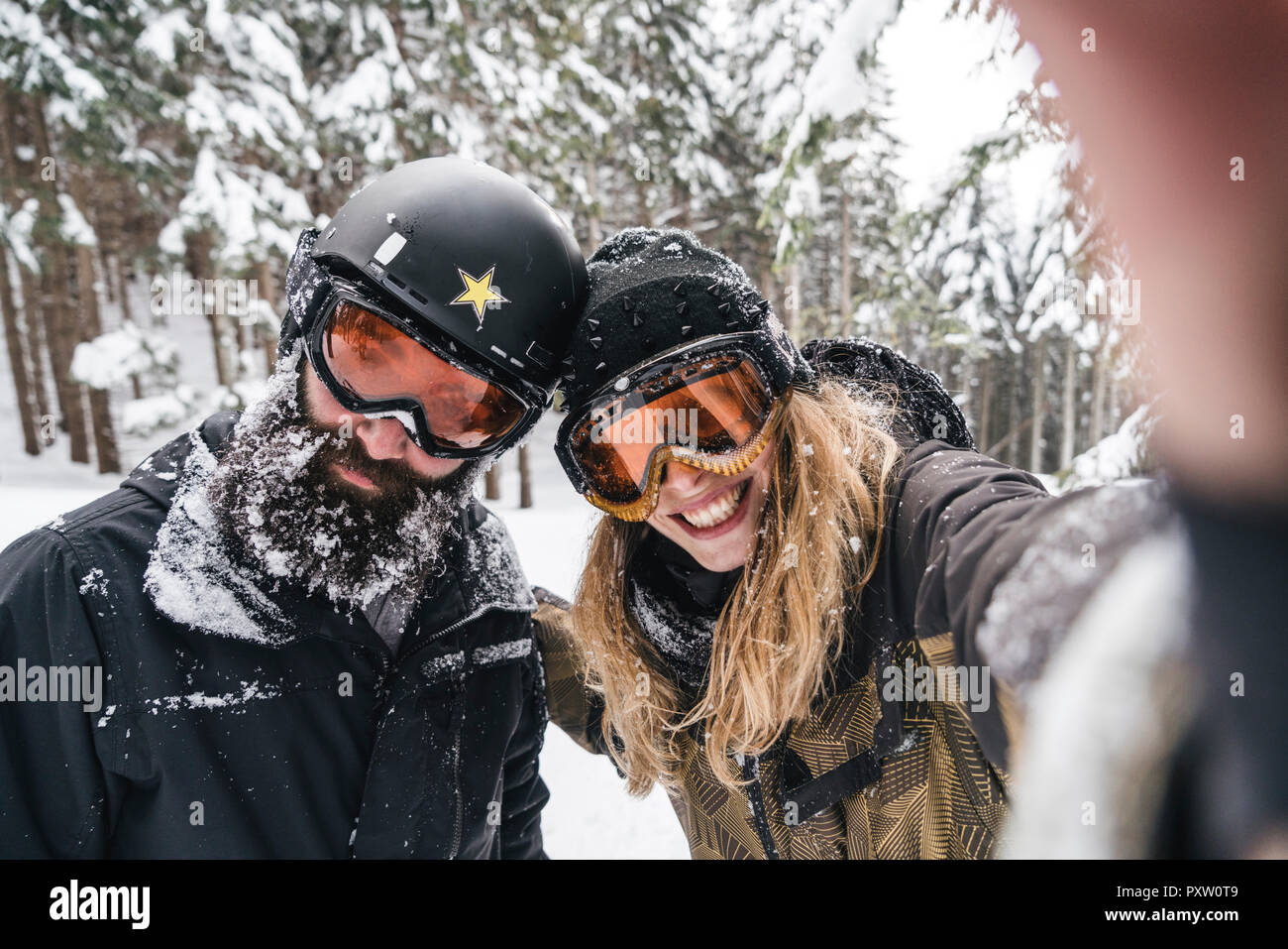 Selfie of smiling couple in skiwear in winter forest - Stock Image