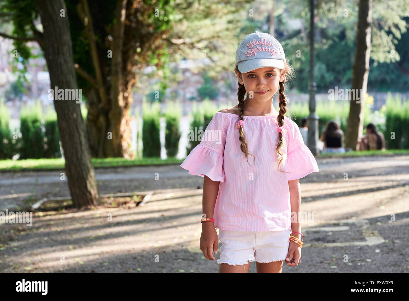 Portrait of smiling little girl with braids and cap - Stock Image