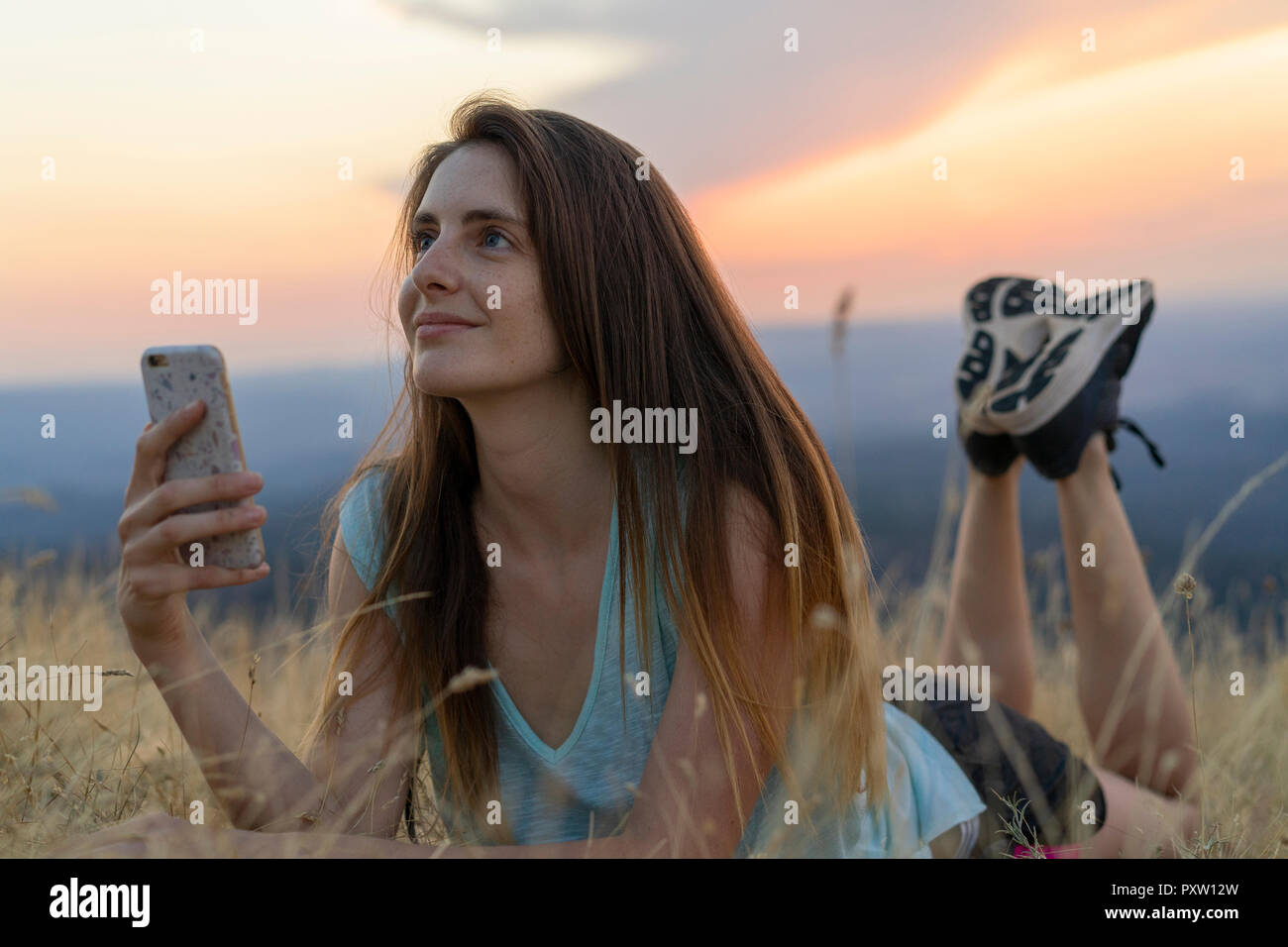 Smiling young woman with cell phone lying in grass during sunset - Stock Image