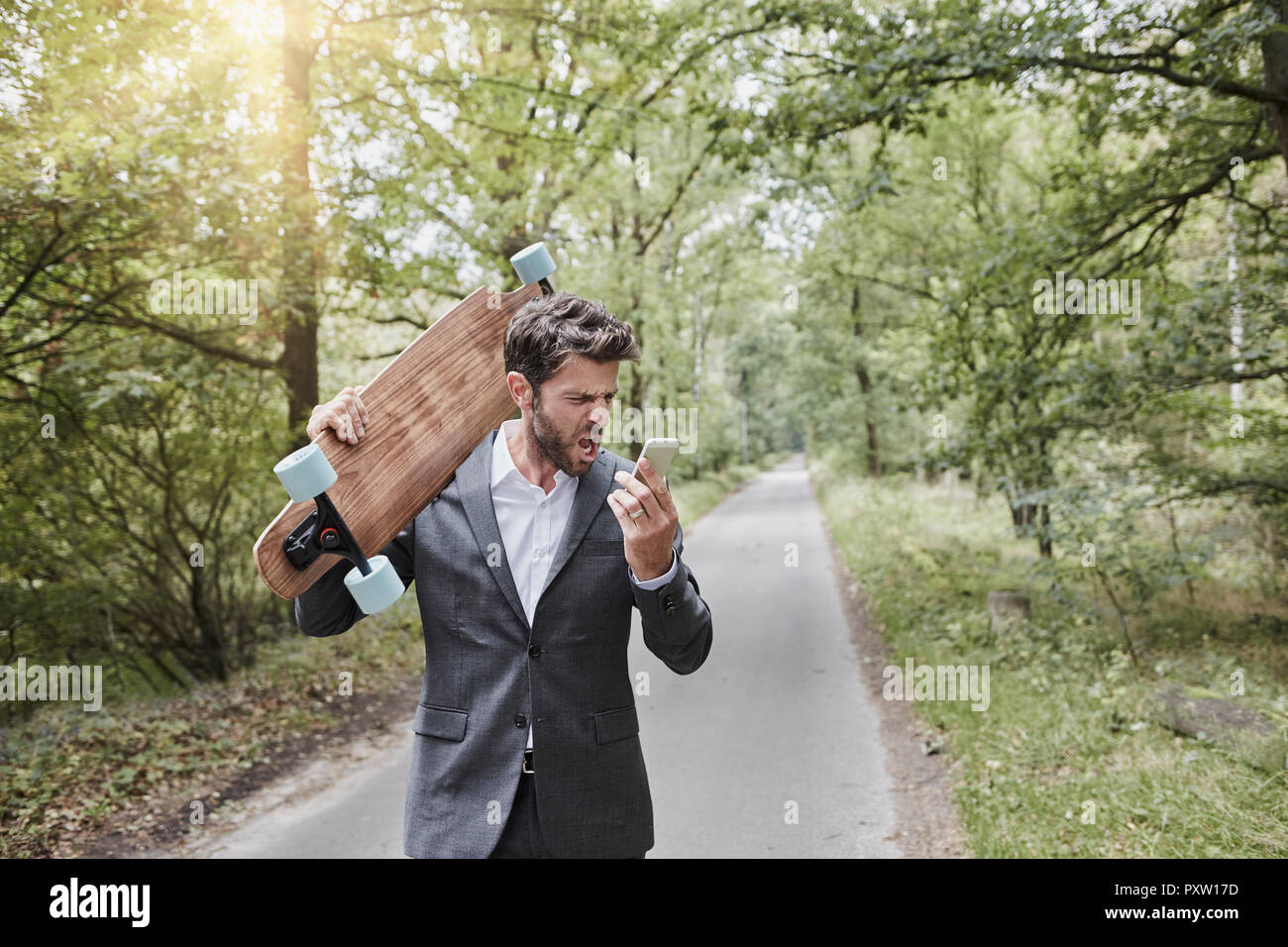 Angry businessman with skateboard shouting at smartphone on rural road - Stock Image
