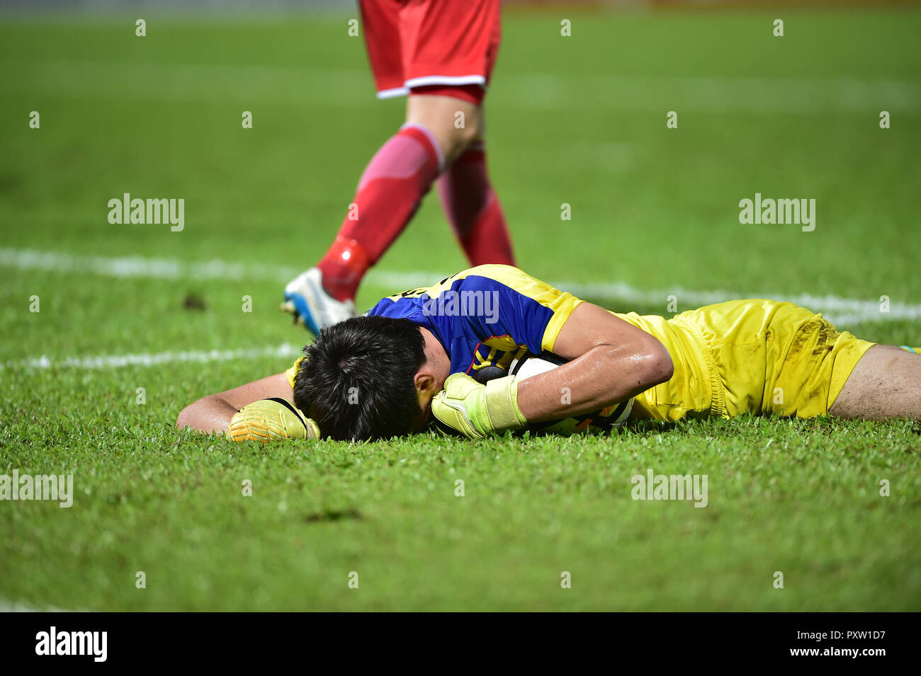 The goalkeeper lies on the ground clutching the ball. - Stock Image