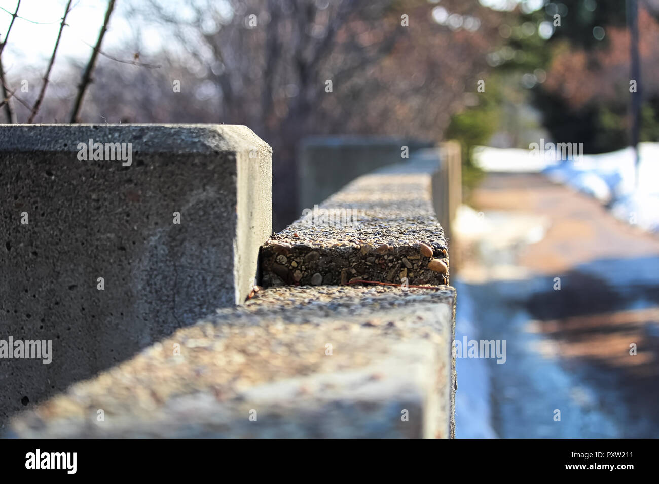 The edge of a cement wall along a footpath in winter - Stock Image