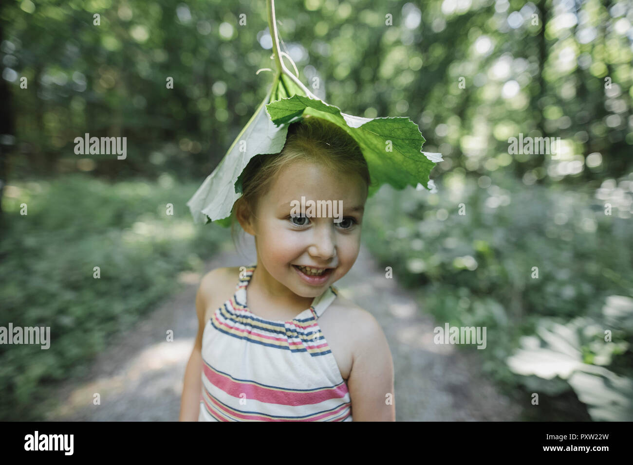 Portrait of smiling little girl with leaf on her head Stock Photo