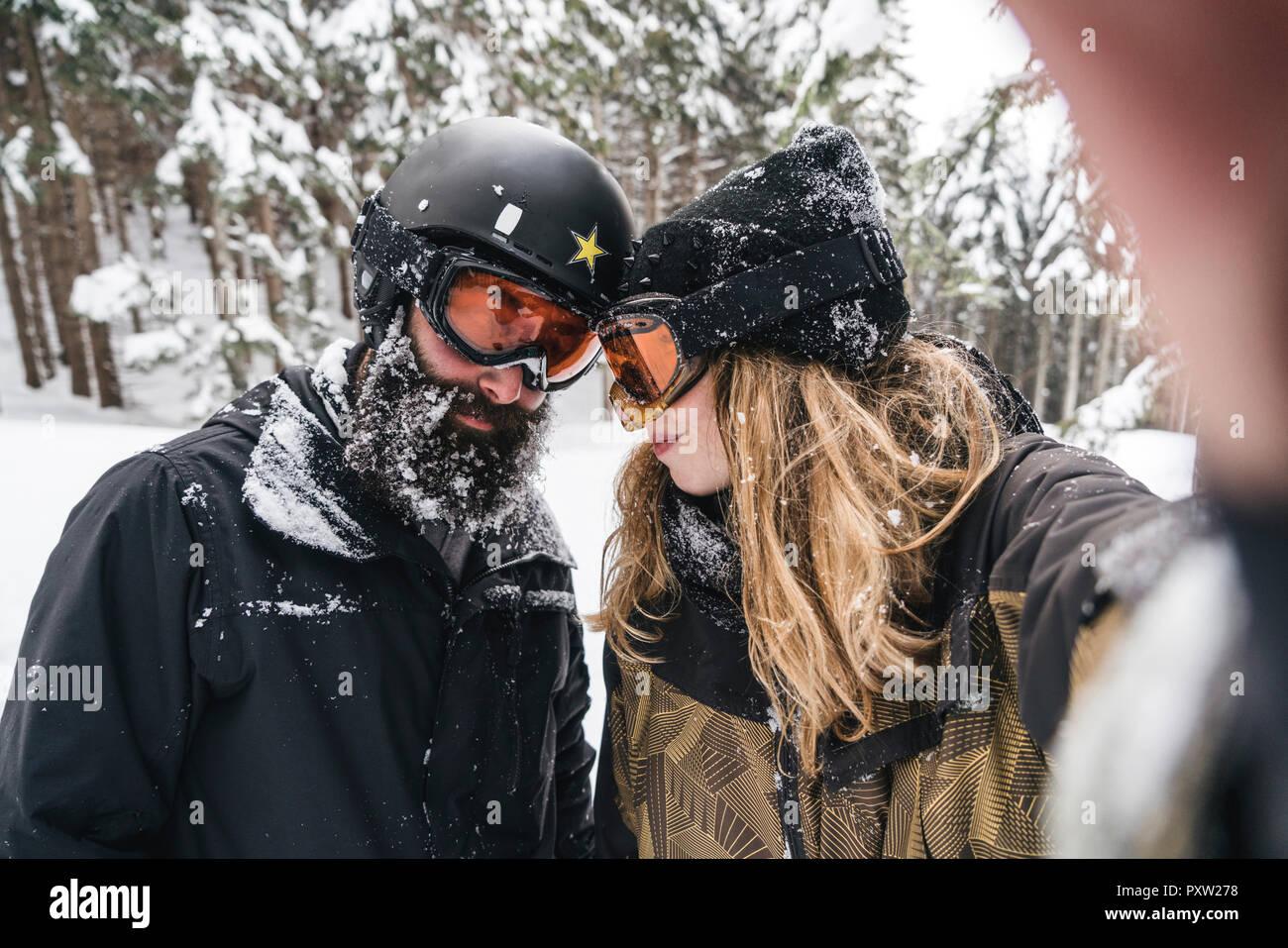Selfie of couple in skiwear in winter forest - Stock Image