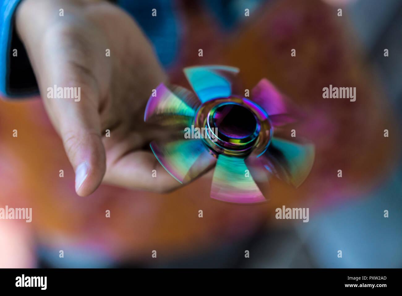 Hand of girl holding rotating Fidget Spinner - Stock Image