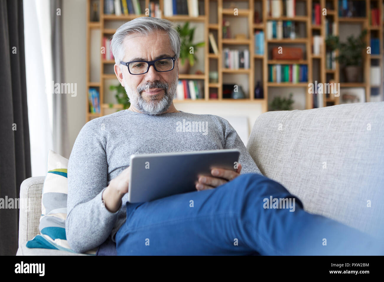 Portrait of mature man sitting on couch at his living room using tablet - Stock Image