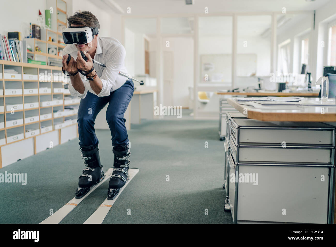 Businessman skiing in office, using VR glasses - Stock Image
