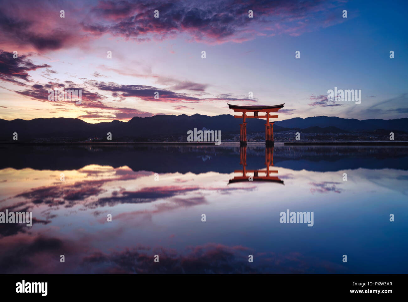 Japan, Hiroshima, Miyajima, Itsukushima Shrine at Seto Inland Sea at sunset - Stock Image