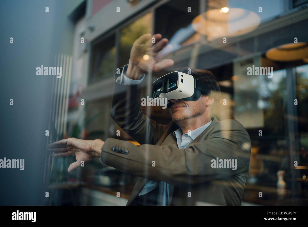 Mature businessman sitting in coffee shop, looking through VR glasses Stock Photo