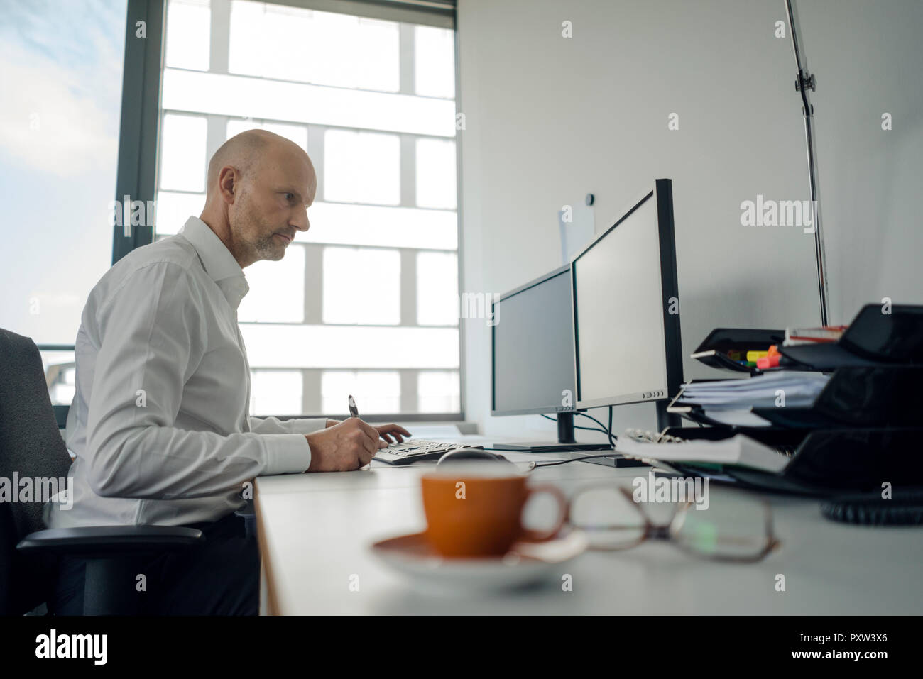 Businessman working on his computer, taking notes - Stock Image