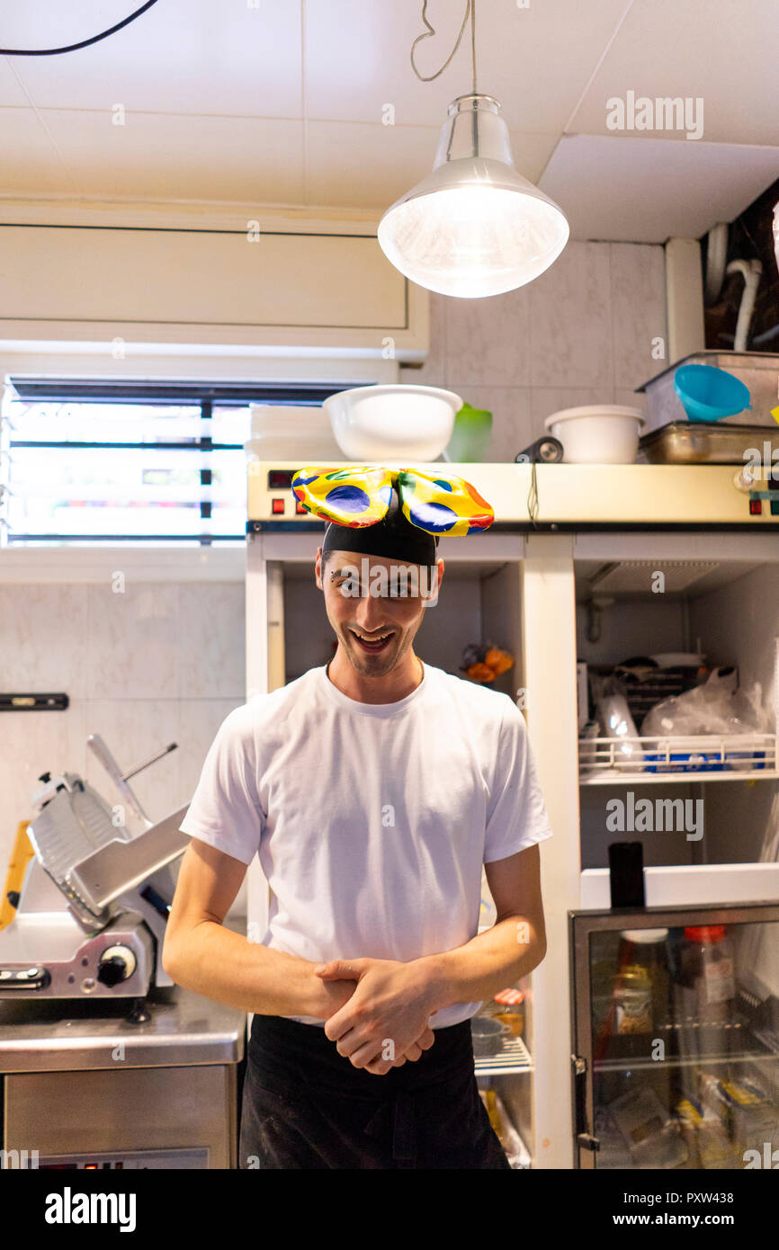 Portrait of funny pizza baker wearing clown's bow tie on his head - Stock Image